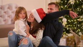 妈妈、爸爸和小小女儿 爱恋的家庭圣诞快乐和新年快乐 快乐的俏丽的人民 父项 股票视频
