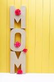 妈妈与康乃馨的文本信件在黄色木背景 免版税图库摄影