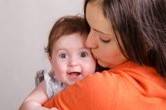 妈妈亲吻一个六个月女儿 免版税图库摄影