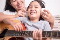 妈妈佩带女孩的白色耳机 免版税库存图片