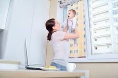 妈妈使用与孩子在窗口在白色厨房里 免版税图库摄影