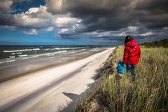 妈妈使用与海滩的孩子 库存图片