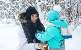 妈妈使用与雪的孩子在冬天 库存照片