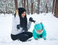 妈妈使用与雪的孩子 库存照片