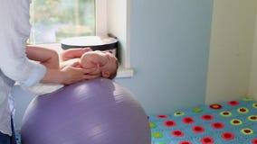 妈妈做发展的锻炼与fitball的婴孩 婴孩发展概念,关心的妈妈,定调子锻炼 股票录像