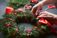 妈妈做圣诞节花圈用她自己的手 库存图片