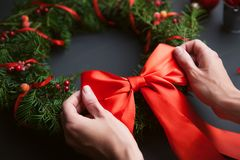 妈妈做圣诞节花圈用她自己的手 免版税库存图片