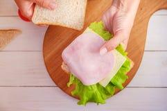 妈妈做学校午餐的一个三明治 免版税图库摄影