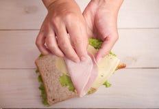 妈妈做学校午餐的一个三明治 免版税库存照片