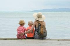 妈妈和两个儿子坐码头并且敬佩海和山在距离 回到视图 免版税库存图片