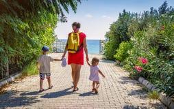 妈妈和两个孩子举行手和步行沿道路到海在清楚,晴朗的夏日在度假 免版税库存照片