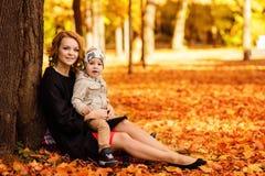 妈妈和儿子公园在秋天 免版税库存图片