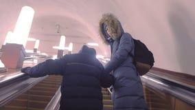 妈妈和儿子冬季衣服的提高自动扶梯在地铁隧道,后面看法 影视素材
