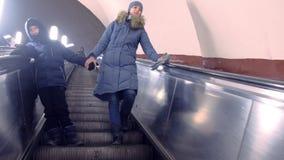 妈妈和儿子冬季衣服的移动在自动扶梯下在地铁隧道 股票视频