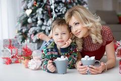 妈妈和儿子在与大杯子的新年树附近说谎热奶咖啡和蛋白软糖 库存照片
