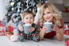 妈妈和儿子在与大杯子的新年树附近说谎热奶咖啡和蛋白软糖 免版税库存照片