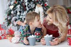 妈妈和儿子在与大杯子的新年树附近说谎热奶咖啡和蛋白软糖 库存图片