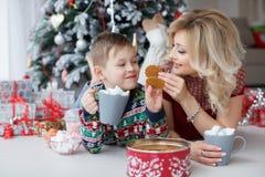 妈妈和儿子在与大杯子的新年树附近说谎热奶咖啡和蛋白软糖 免版税库存图片