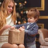 妈妈和儿子在圣诞树附近 图库摄影