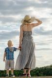 妈妈和儿子在小山站立并且调查距离反对天空,从后面的看法 免版税库存照片