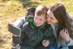 妈妈和儿子在手机做selfie在春天公园 免版税库存图片