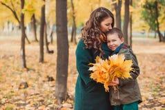 妈妈和儿子在秋天公园走 愉快的系列 秋天概念查出的白色 免版税图库摄影
