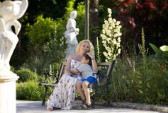 妈妈和儿子坐一条长凳在公园 免版税库存图片