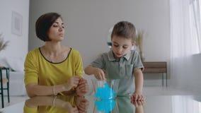 妈妈和儿子坐使用在桌上和笑使用一个有弹性玩具的地板 影视素材