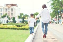 妈妈和儿子手拉手采取 免版税库存图片