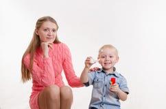 妈妈和儿子打击泡影 图库摄影