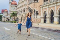 妈妈和儿子苏丹阿卜杜勒萨玛德大厦背景的在吉隆坡,马来西亚 旅行与儿童概念 免版税库存图片