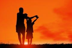 妈妈和儿子获得乐趣在日落,家庭愉快的时光,亚洲孩子,现出轮廓孩子在日落 库存照片