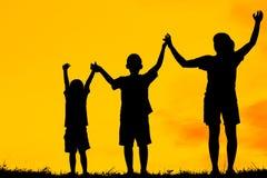 妈妈和儿子获得乐趣在日落,家庭愉快的时光,亚洲孩子,现出轮廓孩子在日落 图库摄影