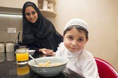 妈妈和儿子阿拉伯家庭食用早餐在厨房 免版税库存照片