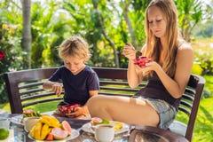 妈妈和儿子食用在大阳台的早餐 免版税图库摄影