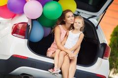 妈妈和女儿一辆汽车的有气球的 免版税库存图片
