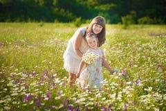 妈妈和女儿一顿野餐的在春黄菊调遣 春黄菊的两个美丽的金发碧眼的女人在马背景调遣  免版税库存图片