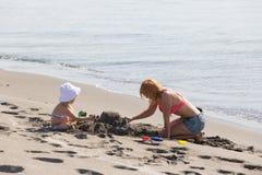 妈妈和女儿修造沙子城堡 免版税图库摄影