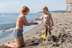 妈妈和女儿修造沙子城堡 免版税库存照片