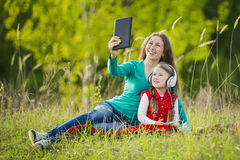 妈妈和女儿做着selfie 免版税图库摄影