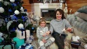 妈妈和女儿升闪烁发光物,家庭在家位于客厅在壁炉和圣诞树附近 股票录像