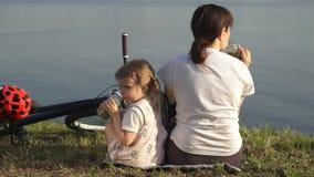 妈妈和女儿喝一个绿色鸡尾酒坐池塘的岸 影视素材