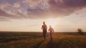 妈妈和女儿在一个美丽如画的地方跑在日落 活跃生活方式和健康家庭 4K慢动作录影 影视素材
