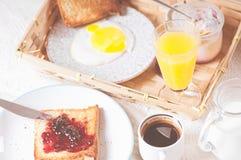 妈妈和女儿在一条白色毯子的床上用早餐 免版税库存图片