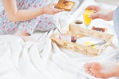 妈妈和女儿在一条白色毯子的床上用早餐 库存照片