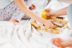 妈妈和女儿在一条白色毯子的床上用早餐 免版税图库摄影