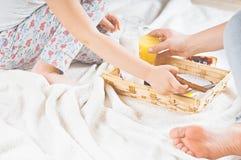 妈妈和女儿在一条白色毯子的床上用早餐 图库摄影