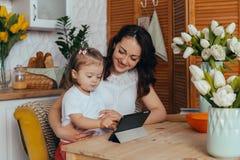 妈妈和女儿在厨房里 免版税库存图片