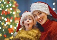 妈妈和女儿在圣诞树附近 免版税图库摄影