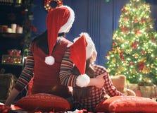 妈妈和女儿在圣诞树附近 免版税库存图片